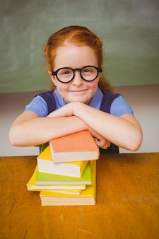 Jolie fille avec une pile de livres dans la salle de classe