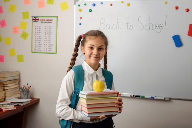 Jolie fille avec une pile de livres à dos debout dans une salle de classe d'une école conventionnelle