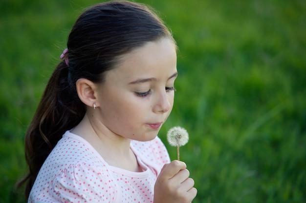 Une jolie fille pissenlit dans l'herbe