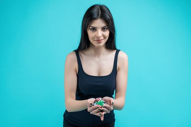 Jolie fille avec une poignée de jetons de poker pour casino en ligne isolé sur turquoise
