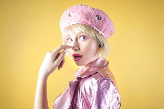 Jolie fille portant des vêtements roses, debout devant un mur jaune