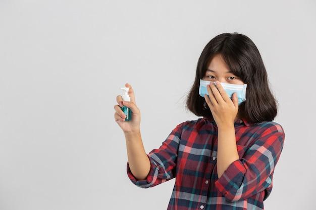 Jolie fille porte un masque et tient le gel des mains en se tenant debout sur le mur blanc.
