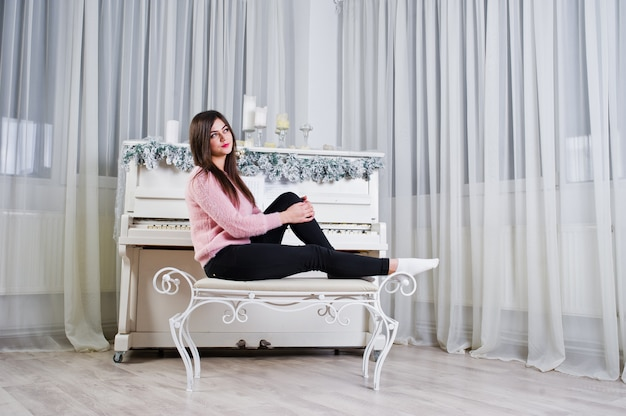 Jolie fille porter sur des chandails chauds et des pantalons noirs contre le vieux piano avec décoration de noël à la salle blanche.