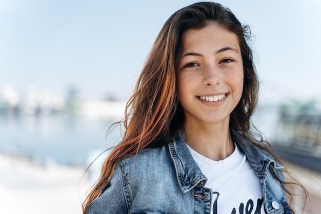 Jolie fille posant dans le contexte de la ville. jolie fille - une adolescente souriante, regardant la caméra, vue rapprochée.