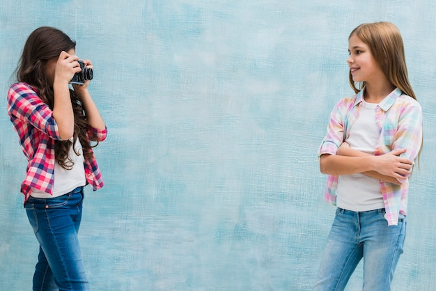 Jolie fille posant devant son amie en train de capturer sa photo avec la caméra sur fond bleu