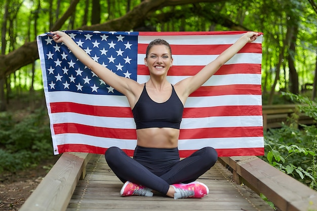 Jolie fille posant avec le drapeau américain dans le parc forestier
