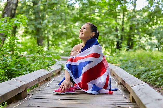 Jolie fille posant avec le drapeau de la grande-bretagne dans un parc forestier