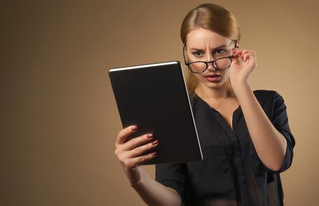 Jolie fille prenant des lunettes et regardant la tablette avec le visage confus