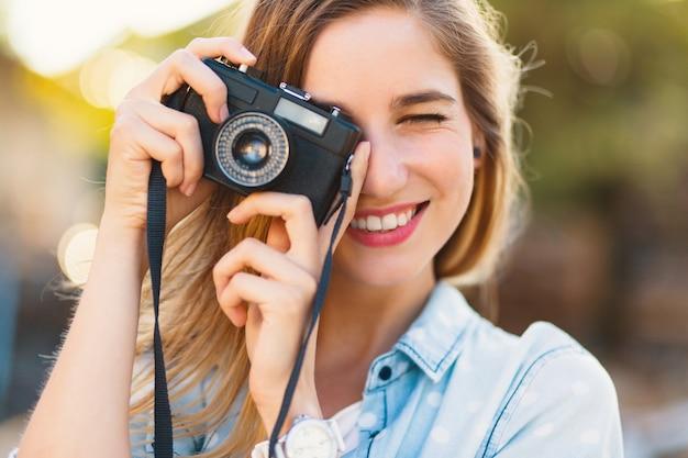 Jolie fille prenant des photos avec un appareil photo vintage sur une journée ensoleillée