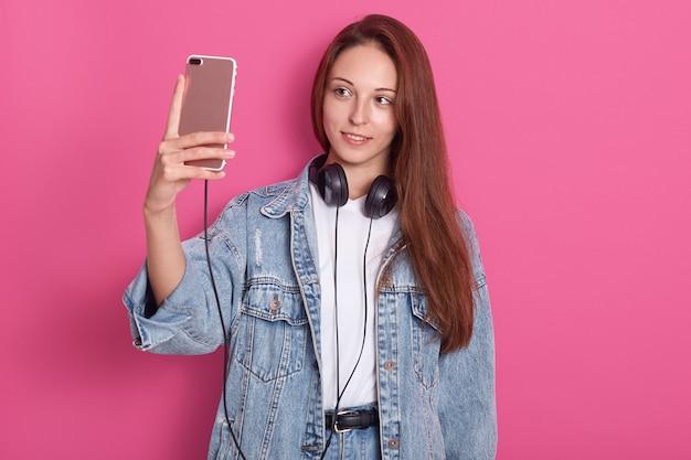 Jolie fille prenant selfie contre le mur du studio rose. femme souriante dans une veste en jean élégante et un t-shirt basique, tenant un smartphone et écoutant de la musique via des écouteurs, en regardant son appareil.