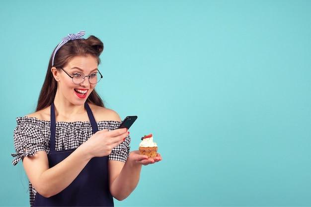Jolie fille prend un petit gâteau à la main sur fond bleu en studio