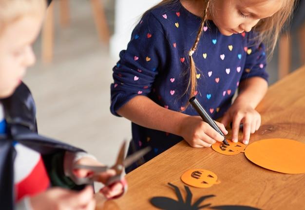 Jolie fille préparant des décorations d'halloween