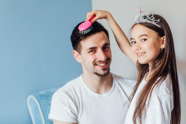 Jolie fille princesse brune fait les cheveux de son père