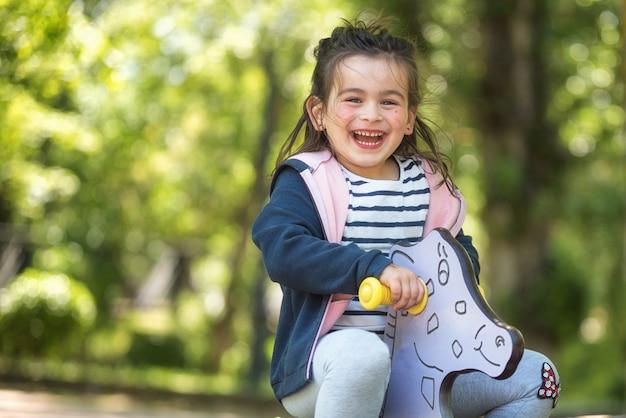 Jolie fille en profitant sur l'aire de jeu dans le parc en été.