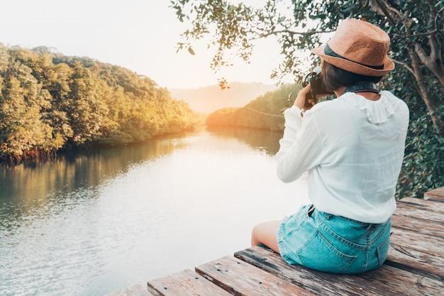 Jolie fille profiter de la nature au repos et en regardant sur la rivière.
