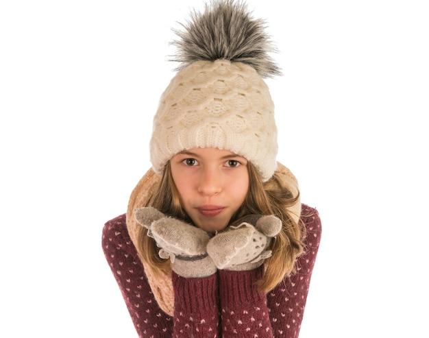Jolie fille en pull, chapeau, écharpe et mitaines envoie un baiser d'air isolé sur blanc