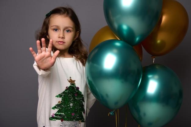 Jolie fille en pull de noël se tient près de belles boules d'air métalliques vertes brillantes et dorées et montre un panneau stop, faisant des gestes avec son doigt, isolé sur fond gris avec espace de copie pour l'annonce