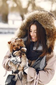 Jolie fille qui marche dans un parc d'hiver avec son chien