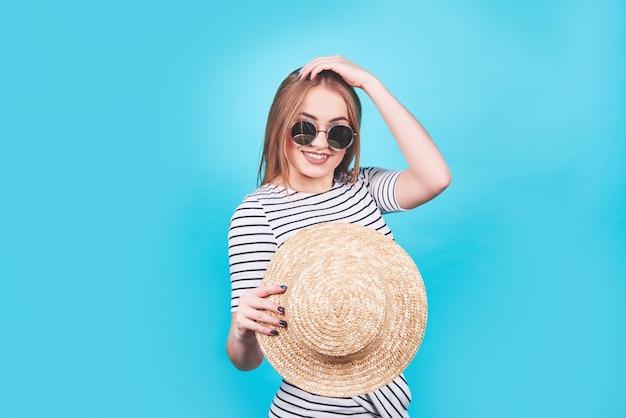 Jolie fille à rayures blanches et noires, chapeau, lunettes de soleil, bouche ouverte avec émotion sur un bleu vif