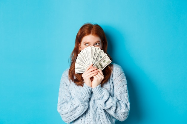 Jolie fille réfléchie aux cheveux rouges rêvant de faire du shopping, tenant des dollars et regardant le logo du coin supérieur gauche, debout sur fond bleu.