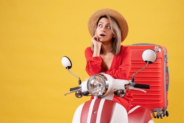 Jolie fille réfléchie sur cyclomoteur avec valise rouge