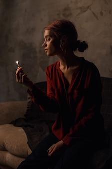 Jolie fille réfléchie dans une chemise rouge avec un décolleté profond avec les cheveux recueillis