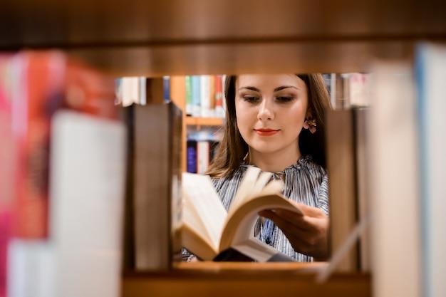 Jolie fille regardant à travers un livre dans la librairie