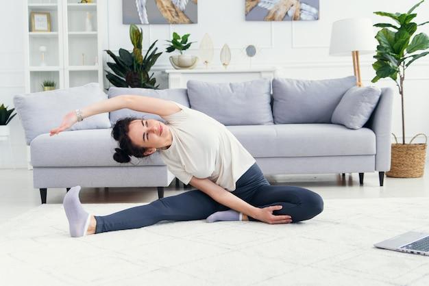 Jolie fille regardant le tutoriel de yoga sur ordinateur portable