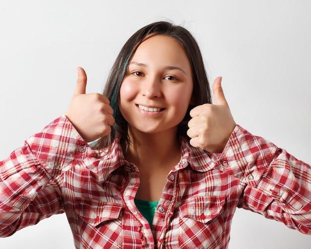 Jolie fille regarde dans le cadre et sourit en montrant les pouces vers le haut du geste des deux mains