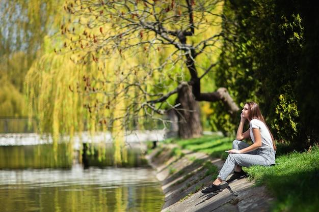 Jolie fille reposant sur la berge près de la forêt au printemps, journée chaude. se détendre sur la nature le week-end. fille en vêtements jeans assis près du lac dans le parc. concept de nature. séance photo de mode. horizontal.