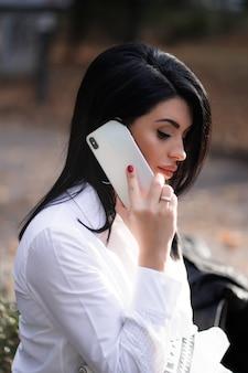 Jolie fille reposant sur la nature le week-end. fille en chemise blanche assise dans le parc. caucasienne brune jeune femme parlant sur smartphone à l'extérieur seul. technologies et gadgets.