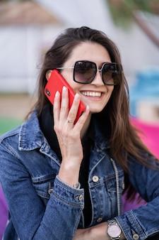 Jolie fille reposant sur la nature le week-end. fille en veste de jeans assis dans le parc. caucasienne brune jeune femme parlant sur smartphone à l'extérieur seul. technologies et gadgets.