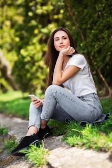 Jolie fille reposant sur la nature le week-end. fille en vêtements jeans assis près du lac dans le parc. brune caucasienne jeune femme avec smartphone à l'extérieur seul.technologies et gadgets.vertical