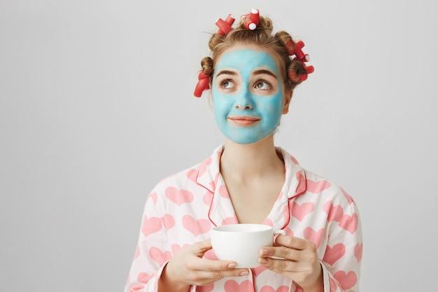 Jolie fille rêveuse en bigoudis et masques faciaux appréciant une tasse de café