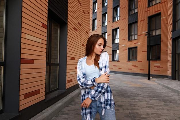 Jolie fille rêveuse dans la ville lors d'une promenade parmi les bâtiments. urbain