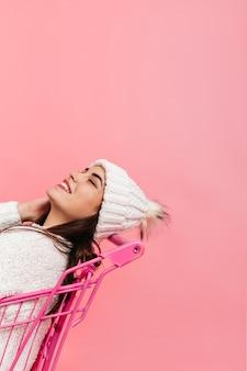 Jolie fille en riant, posant dans un chariot de supermarché rose. plan d'une brune en vêtements d'hiver blancs sur un mur isolé.