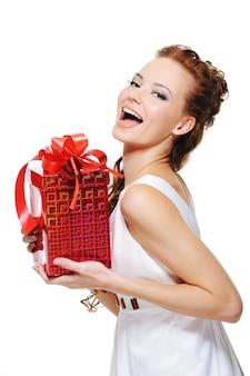 Jolie fille en riant tenant la boîte rouge présente sur fond blanc