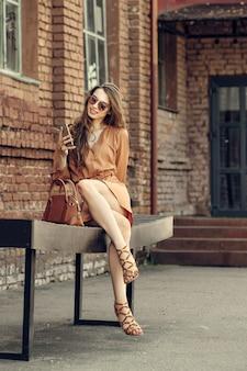 Jolie fille en robe courte assis sur un banc avec smartphone à la main
