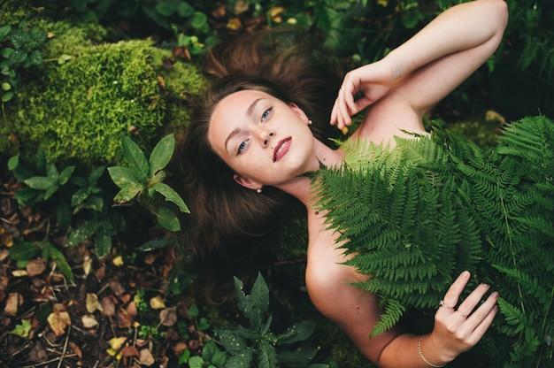 Une jolie fille en robe à fleurs est assise avec un bouquet de fougère dans la forêt.