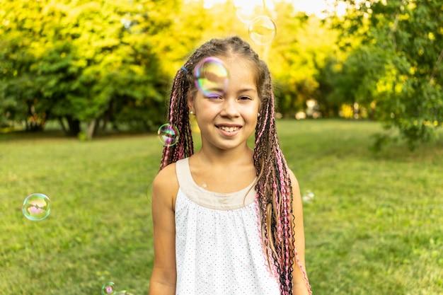 Jolie fille en robe et avec des nattes africaines est debout dans un parc sur fond de bulles de savon