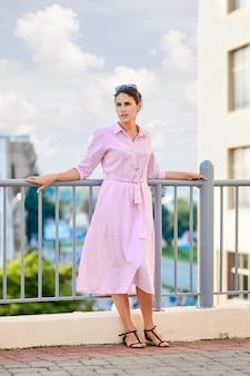 Jolie fille en robe rayée rouge et lunettes de soleil debout sur le balcon
