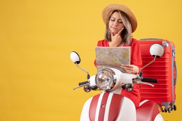 Jolie fille en robe rouge sur cyclomoteur avec valise en regardant la carte