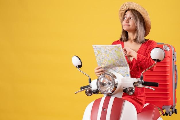 Jolie fille en robe rouge sur cyclomoteur avec valise rouge tenant la carte