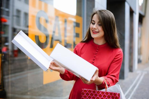 Jolie fille en robe rouge heureuse d'acheter des chaussures à la mode pendant une période de vente