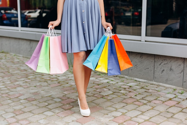 Jolie fille en robe tenant des sacs multicolores