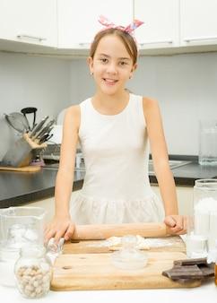 Jolie fille rouler la pâte avec une épingle en bois dans la cuisine