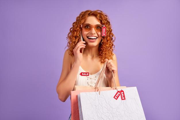Jolie fille rousse avec des boucles et des étiquettes de vente parle par téléphone isolé sur violet