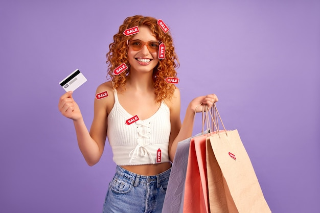 Jolie fille rousse avec des boucles, des sacs à provisions et des étiquettes de vente montrant une carte de crédit isolée sur violet