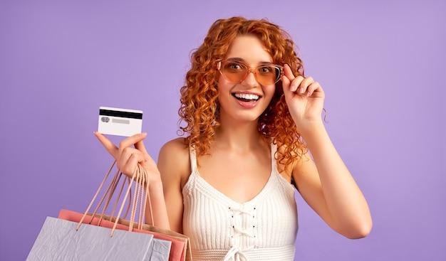 Jolie fille rousse avec des boucles et des sacs à provisions tenant une carte de crédit isolée sur violet. shopping en ligne. vente
