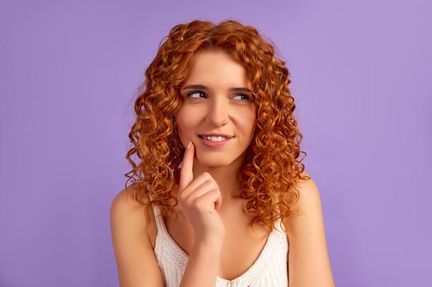 Une jolie fille rousse avec des boucles tient un doigt sur sa joue, pense à quelque chose ou à des rêves, a quelque chose en tête, isolée sur violet